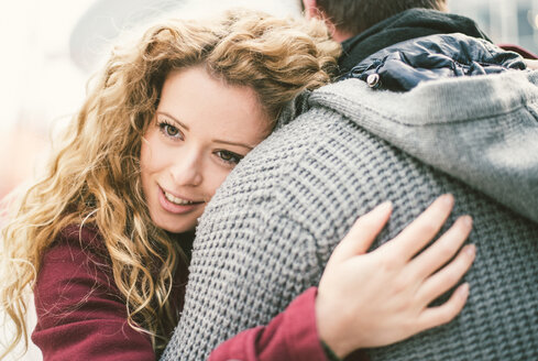 Portrait of smiling young woman hugging her boyfriend - OIPF000014