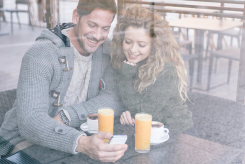 Happy couple sitting in a coffee shop looking at smartphone - OIPF000020
