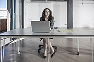 Businesswoman sitting at desk using laptop - ZEF007559