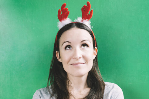 Portrait of smiling woman wearing hair-band with red reindeer antlers in front of green wall - GEMF000546