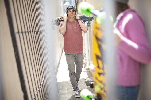 Friends with skateboards in a passageway - ZEF007577