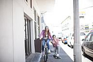 Teenage girl on bicycle pushing young man on skateboard - ZEF007592