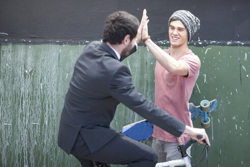 Young man with skateboard high fiving with businessman on bicycle - ZEF007601