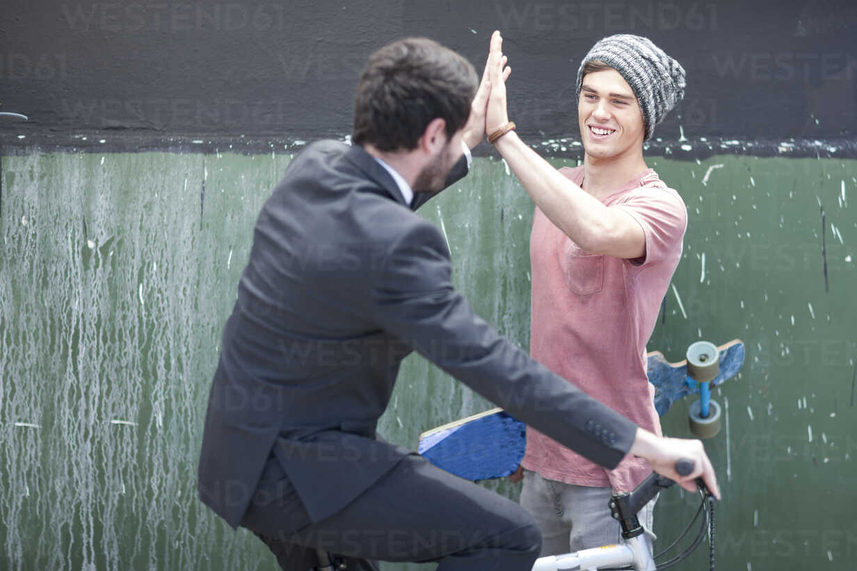 Young man with skateboard high fiving with businessman on bicycle - ZEF007601 - zerocreatives/Westend61