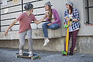 Young man with friends riding skateboard - ZEF007604