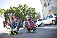 Two friends sitting on skateboards riding down the street - ZEF007616