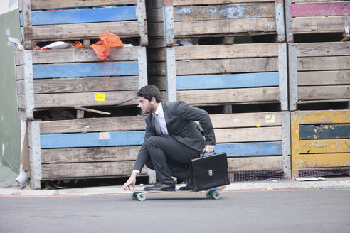 Businessman riding on skateboard - ZEF007622