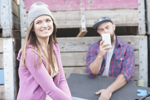 Smiling teenage girl and young man with skateboard - ZEF007625