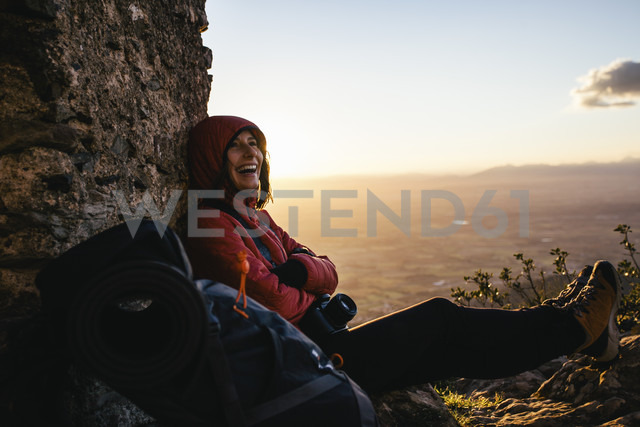 Spain, Catalunya, Girona, happy female hiker resting at stone structure - EBSF001166 - Bonninstudio/Westend61