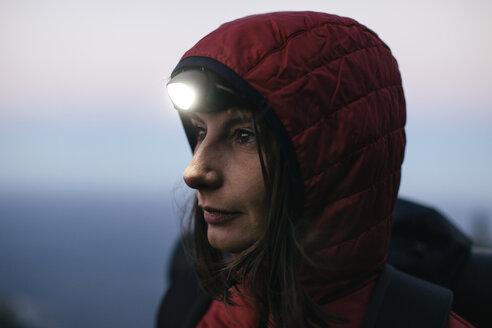 Female hiker wearing headlamp at twilight - EBSF001172