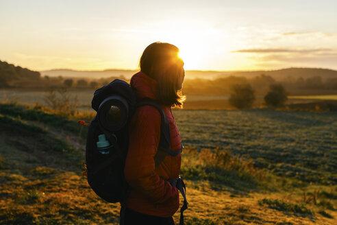 Spain, Catalunya, Girona, female hiker on field at sunrise - EBSF001178
