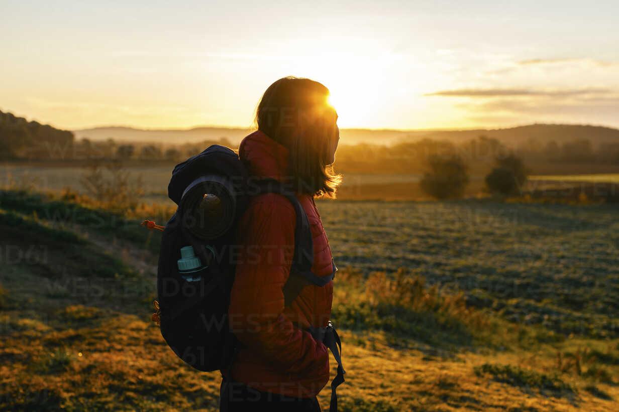 Spain, Catalunya, Girona, female hiker on field at sunrise - EBSF001178 - Bonninstudio/Westend61