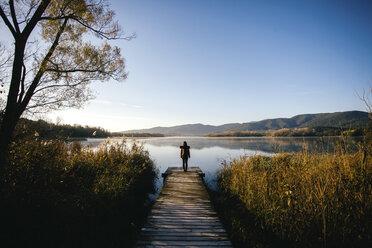 Spain, Catalunya, Girona, female hiker on jetty at a lake enjoying the nature - EBSF001184