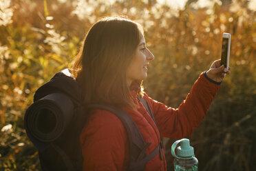 Spain, Catalunya, Girona, smiling female hiker holding cell phone - EBSF001187