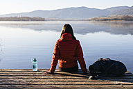 Spain, Catalunya, Girona, female hiker resting on jetty at a lake enjoying the nature - EBSF001190