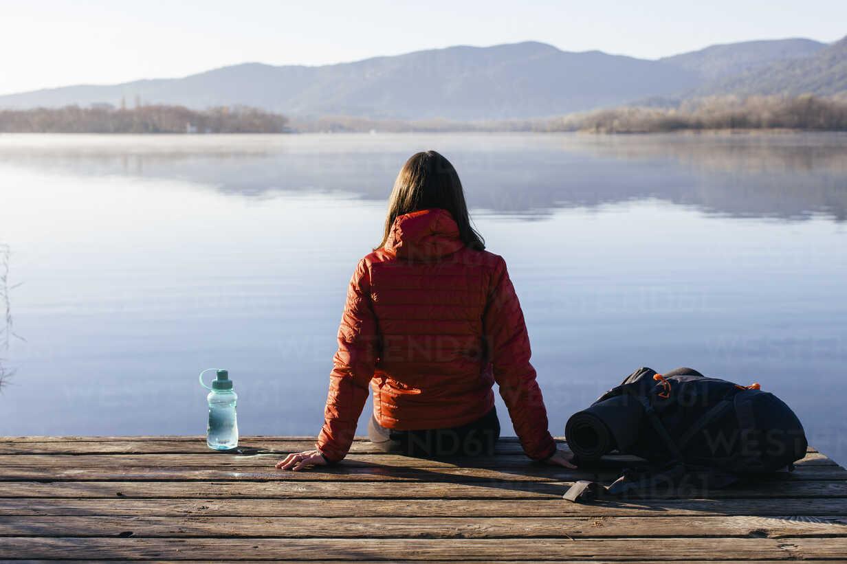 Spain, Catalunya, Girona, female hiker resting on jetty at a lake enjoying the nature - EBSF001190 - Bonninstudio/Westend61