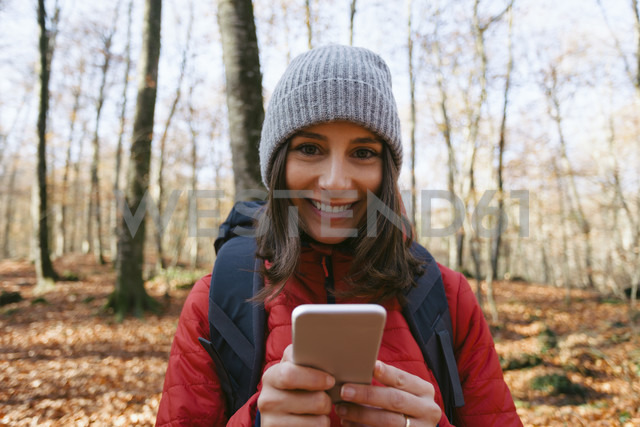 Spain, Catalunya, Girona, portrait of smiling female hiker in the woods with cell phone - EBSF001199 - Bonninstudio/Westend61