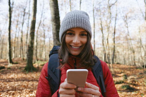 Spain, Catalunya, Girona, portrait of smiling female hiker in the woods with cell phone - EBSF001199