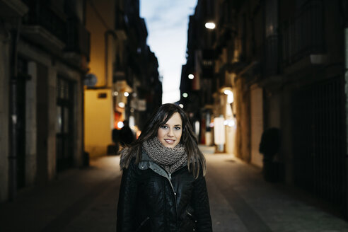 Spain, Reus, portrait of smiling young woman standing in an alley in the evening - JRFF000244