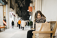 Spain, Reus, happy young woman sitting on a bench with her shopping bags - JRFF000247