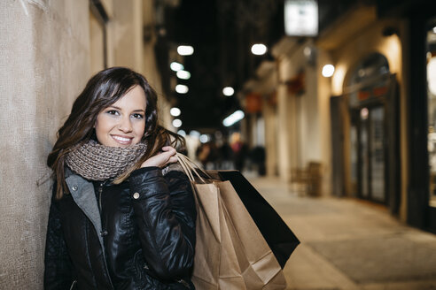 Spain, Reus, portrait of smiling young woman with shopping bags leaning at house facade at night - JRFF000250