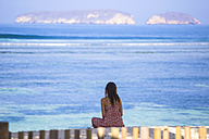 Indonesia, Sumbawa, young woman sitting on the beach looking at the sea - KNTF000219