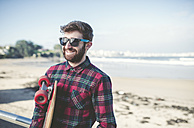 Spain, La Coruna, portrait of smiling hipster wearing sunglasses with his skateboard on the beach - RAEF000727
