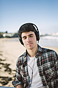 Spain, La Coruna, portrait of young man with headphones on the beach - RAEF000730