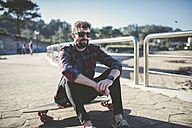 Spain, La Coruna, portrait of hipster wearing sunglasses sitting on his longboard - RAEF000733