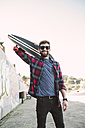 Spain, La Coruna, portrait of smiling hipster wearing sunglasses holding  longboard on his shoulder - RAEF000739