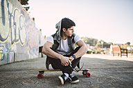 Spain, La Coruna, young man sitting on his longboard - RAEF000742