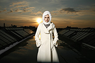 Portrait of woman wearing white coat and hood standing on a roof at evening twilight - TMF000090