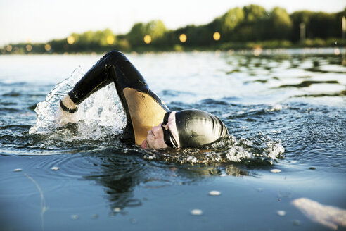 Triathlete swimming in lake - JATF000797