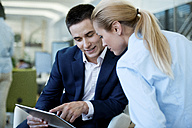 Businessman and businesswoman looking at digital tablet in office - WESTF021590