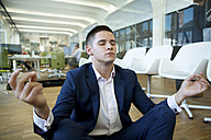 Young businessman meditating in office - WESTF021605