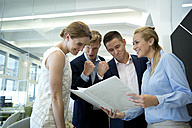 Successful business team in office looking at folder - WESTF021608