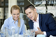 Smiling businessman talking to colleague - WESTF021614