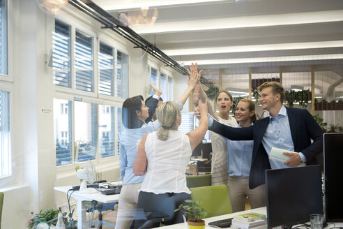 Successful business team high fiving in office - WESTF021623