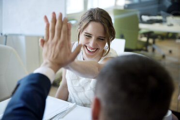 Happy businesswoman and businessman high fiving - WESTF021641