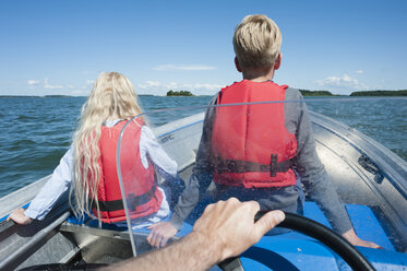 Finland, Turku archipelago, Houtskaer, father and his two children driving in motorboat - JBF000261