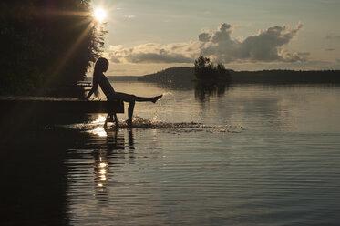 Finland, Karelia, Uukuniemi, Lake Pyhäjärvi, girl sitting on jetty splashing with her feet in the water - JBF000264