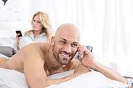 Mature couple in bedroom using their mobile phones - MAEF011077