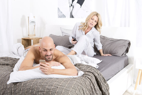Mature couple in bedroom using their mobile phones - MAEF011080
