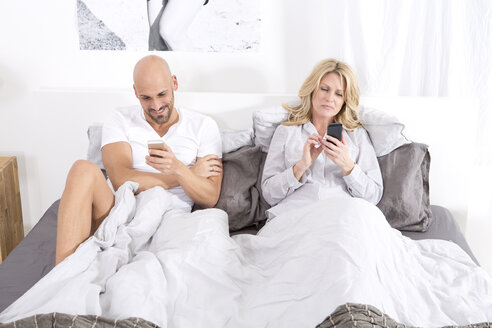 Mature couple sitting in bed using smartphones - MAEF011083