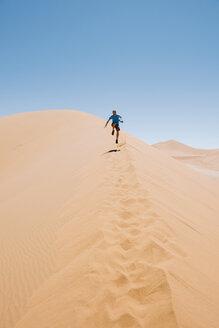 Namibia, Namib Desert, Sossusvlei, Man running down a dune - GEMF000553