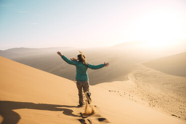 Namibia, Namib Desert, Sossusvlei, Woman running down the Dune 45 at sunrise - GEMF000559