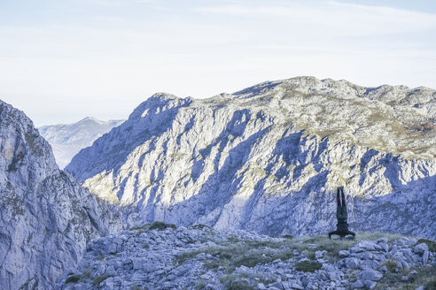 Spain, Asturias, Man doing a handstand with mountain landscape in the background, Picos de Europa - ABZF000172