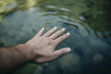 Man's hand touching water surface of a mountain pond - JRFF000259