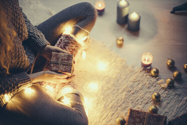 Woman sitting with Christmas present and fairy lights on the carpet - JPF000086