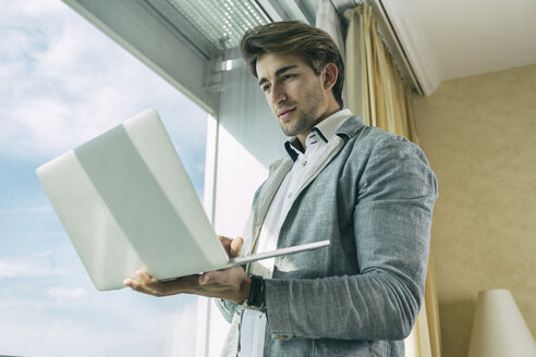 Portrait of young businessman standing in front of a window holding laptop - TAMF000349